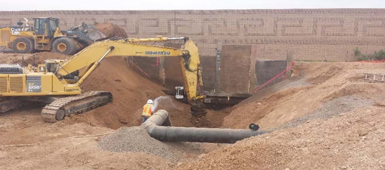 Worker and crane working in hole around a pipe in chandler az